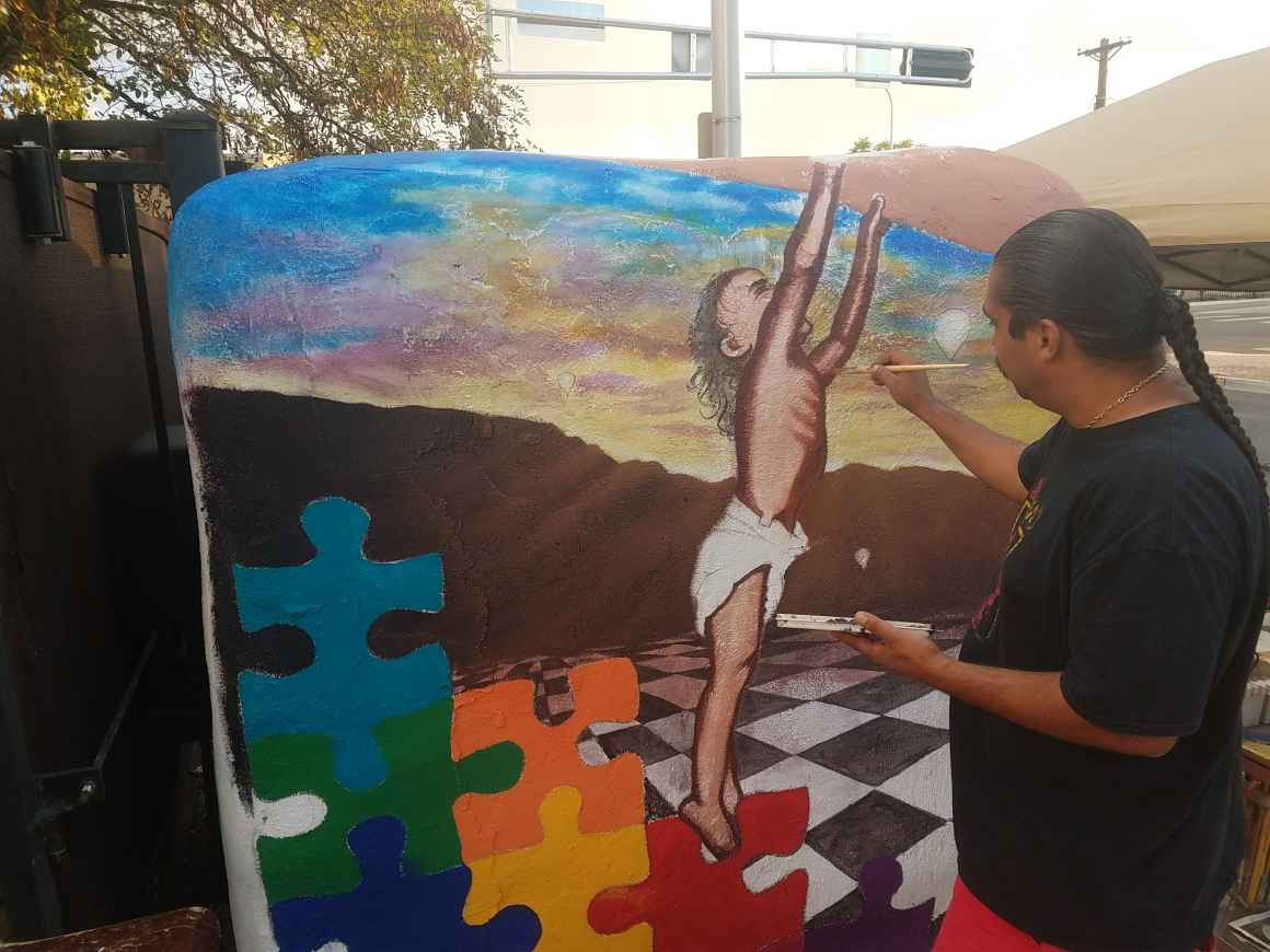 Eric Christo Martinez painting at 508 Mural Fest