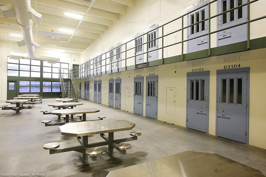 An empty cell block in a prison with tables and blue doors.