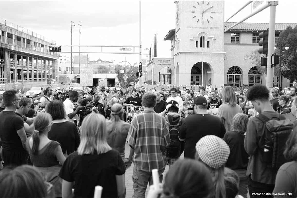 Photo: Black and white image of a group of people gathered in a circle on a street corner
