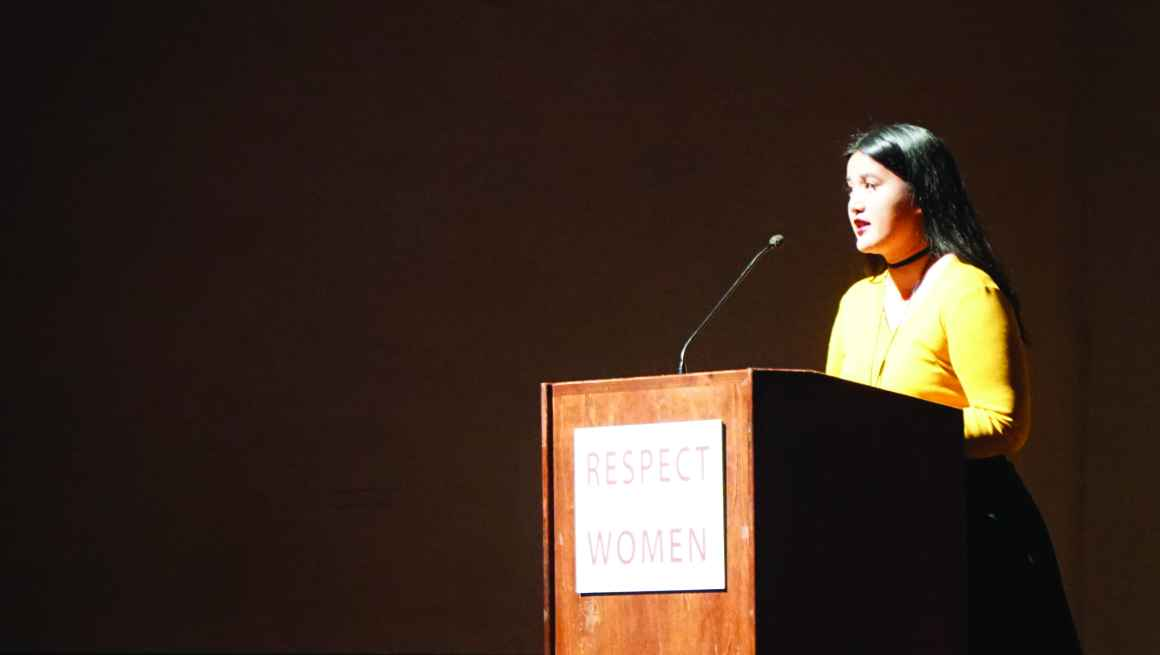 Photo: A woman stands behind a podium speaking to a crowd