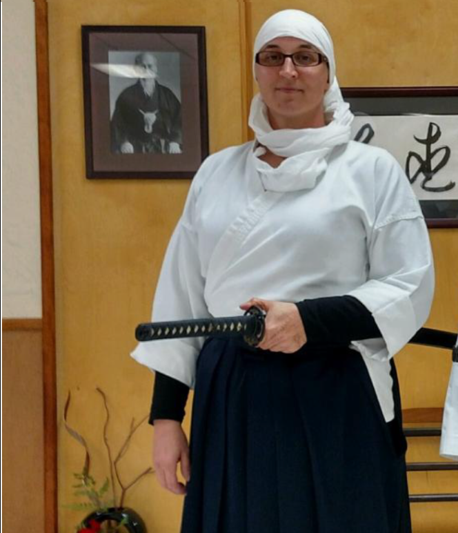 A woman stands wearing a white headscarf and martial arts robe, holding a sword