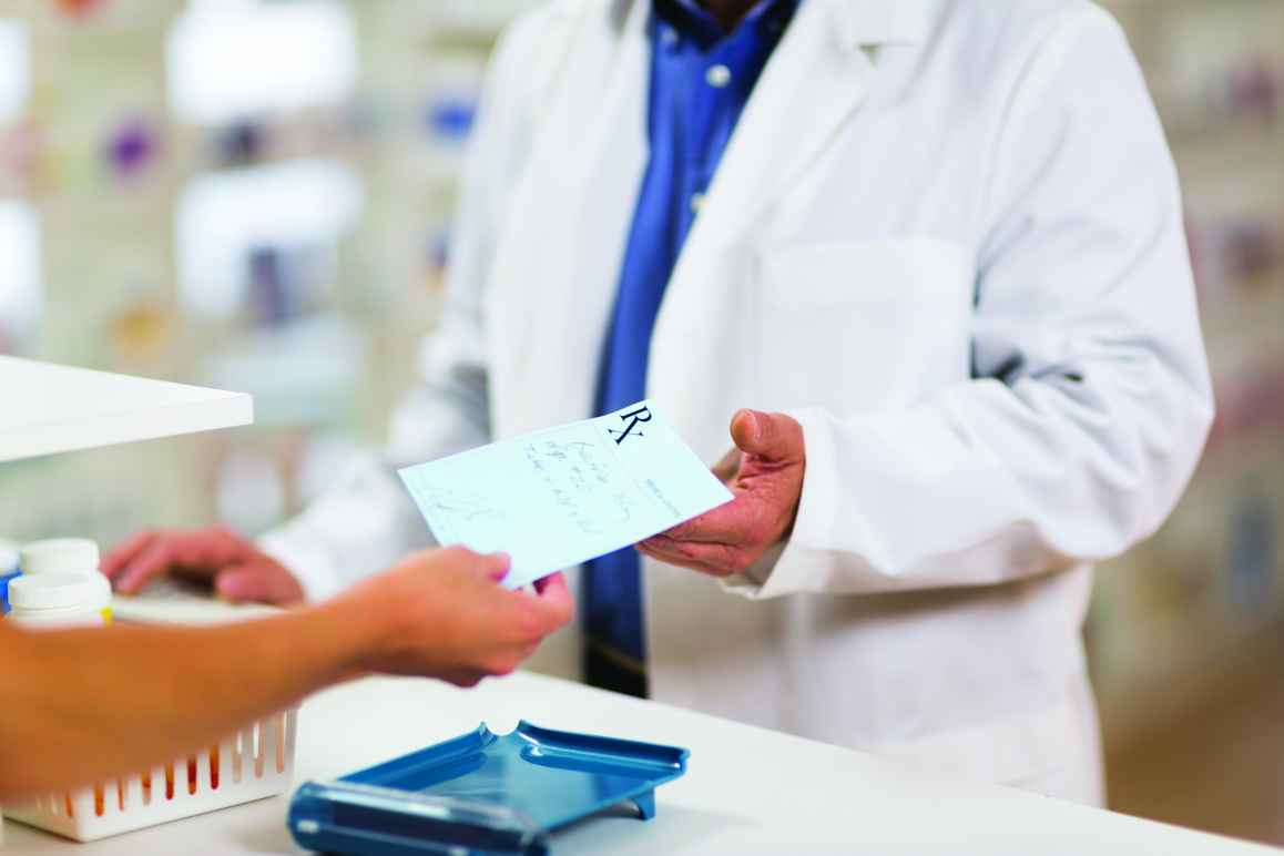 Photo: cropped photo of a pharmacist in a white coat behind a counter receiving a paper prescription from an outstretched hand