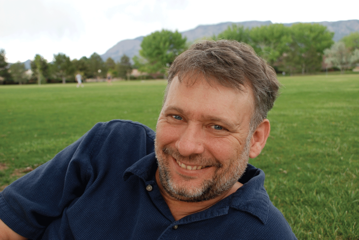 Photo: A man with short hair and groomed facial hair in a navy blue polo shirt reclining on a field of grass, smiling at the camera