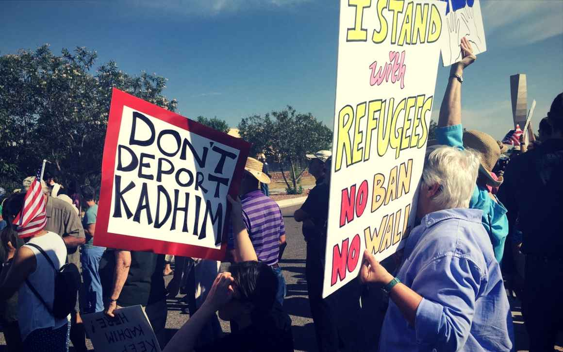 """Protesters hold posters that read """"Don't deport Kadhim"""" and """"I stand with refugees.  No ban. No wall."""""""