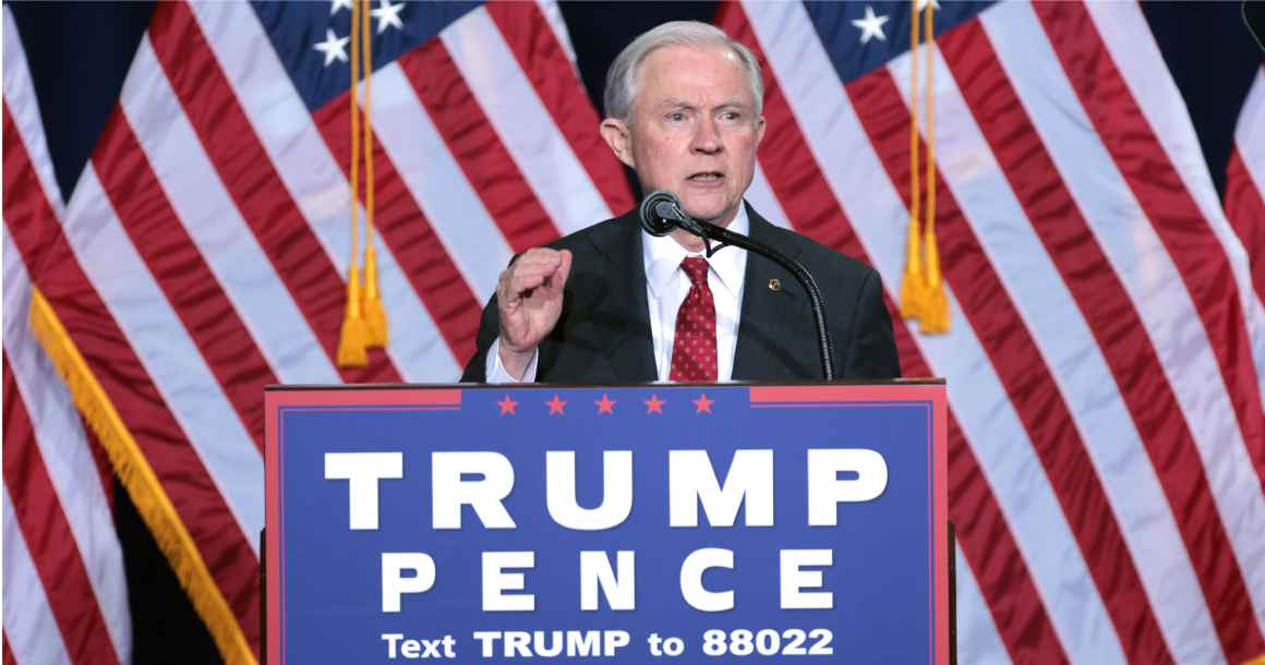 AG Jeff Sessions behind a podium speaking at a Trump Pence political rally