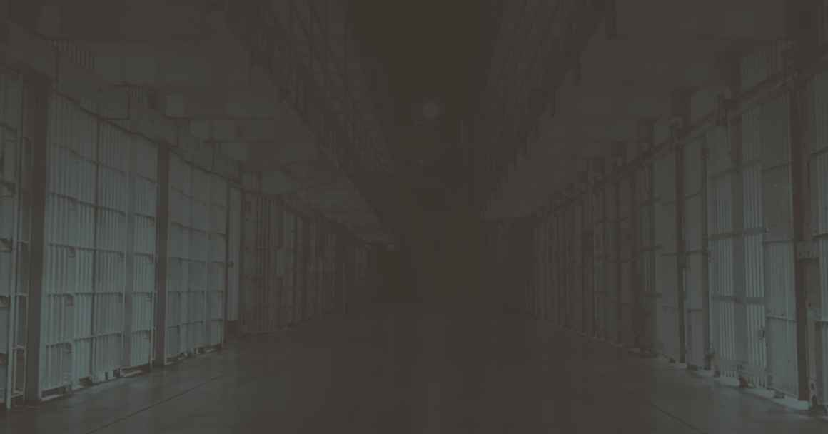 Dark hallway with prison cells.